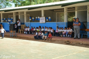 The preschool students waiting for the ribbon on their classroom to be cut.