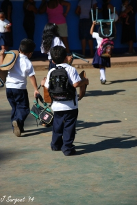 Preschool students carry their chairs to their new classroom